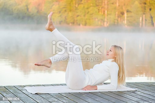 873786782 istock photo Woman relaxing and practicing yoga in the mist. Early morning. 610981924