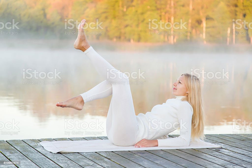 Woman relaxing and practicing yoga in the mist. Early morning. stock photo