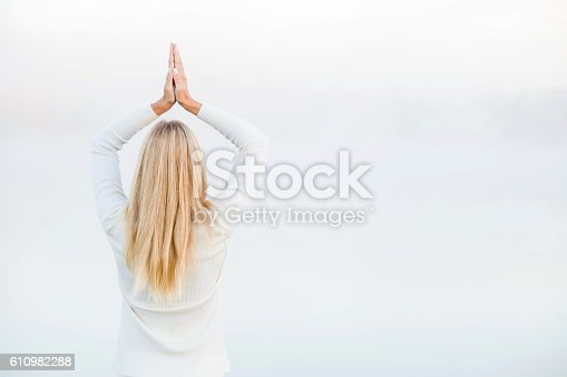 873786782 istock photo Woman relaxing and practicing yoga in the mist. Early morning. 610982288