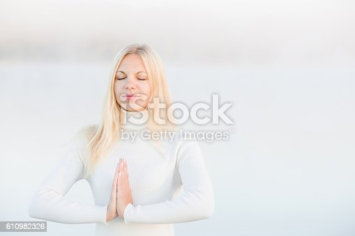 873786782 istock photo Woman relaxing and practicing yoga in the mist. Early morning. 610982326