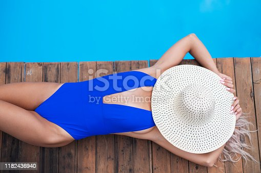 Unrecognizable sexy woman laying on back around poolside on wooden lounge and relaxing, she having summer hat on her face.