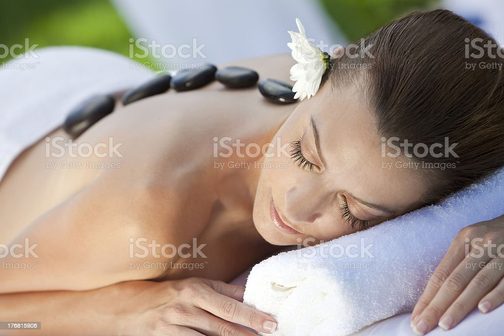 Woman relaxing at a health spa having a hot stone massage stock photo