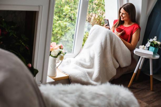 Frau entspannt zu Hause und mit einem Videoanruf mit Freunden – Foto