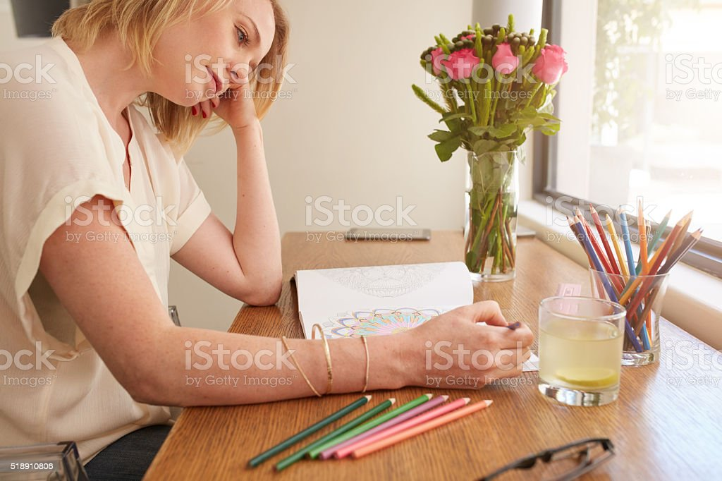 Woman relaxing at home by coloring book stock photo