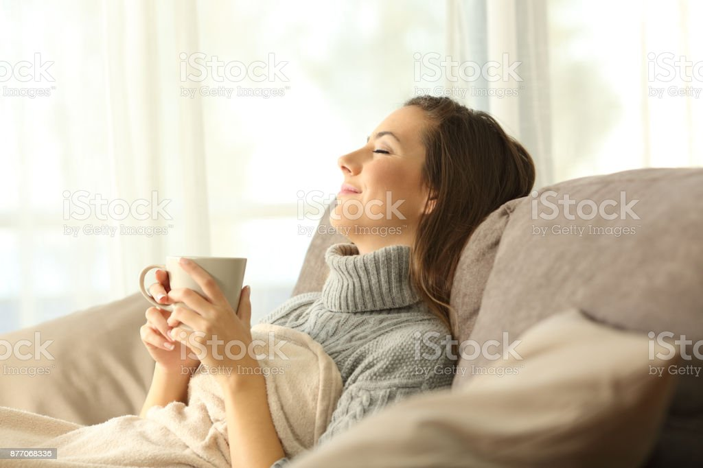 Woman relaxing at home holding a coffee mug stock photo