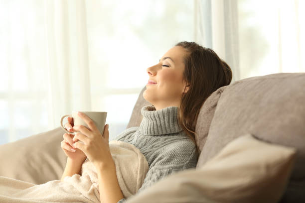 Woman relaxing at home holding a coffee mug Woman relaxing holding a coffee mug sitting on a sofa in the living room in a house interior relief emotion stock pictures, royalty-free photos & images