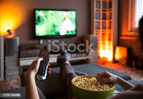 504821746 istock photo Woman relaxing at home watching tv and eating popcorn and surfing internet 1225739486