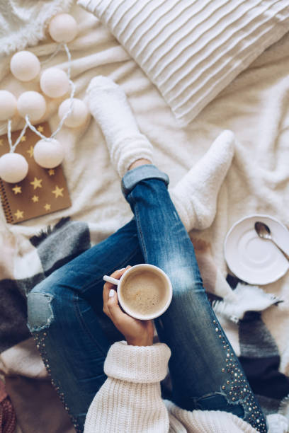woman relaxing at home with a cup of coffee - hygge imagens e fotografias de stock