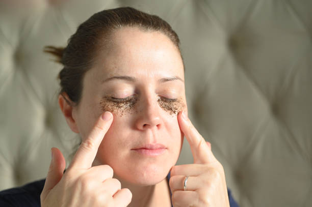 Woman relaxing at home with coffee grounds on her face stock photo