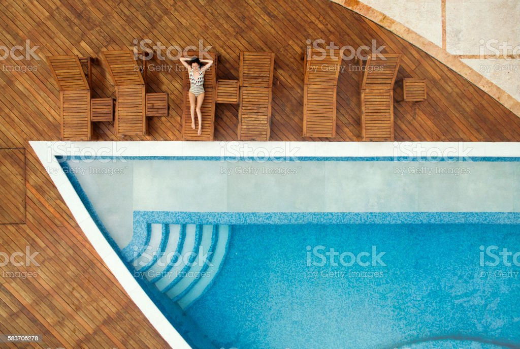 Woman relaxing at swimming pool stock photo