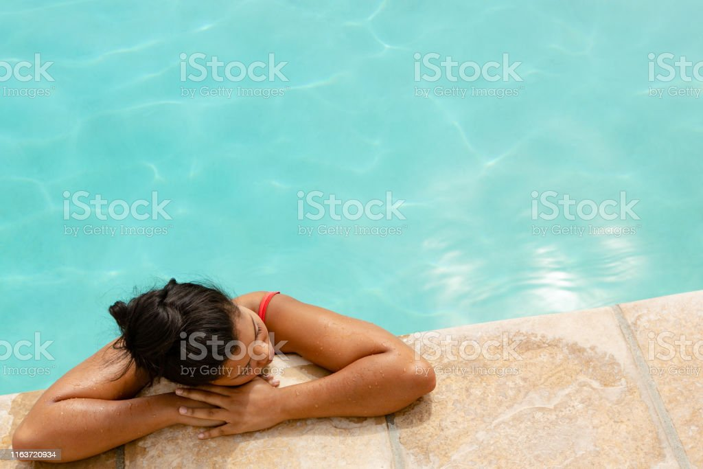 Aerial view of mixed-race woman relaxing at the edge of swimming pool...