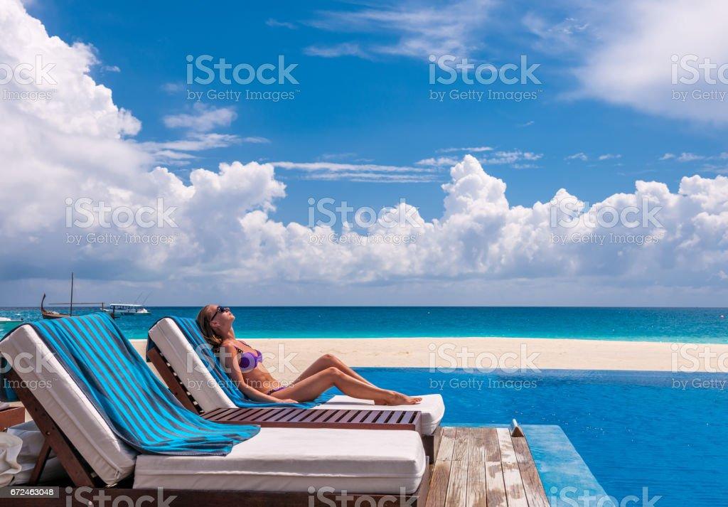 Woman relaxing at the poolside - foto de acervo
