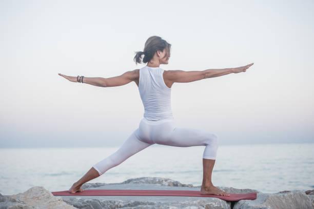 Frau Entspannen im Sonnenuntergang durch Üben Eka Pada Yoga am Felsigen Strand – Foto