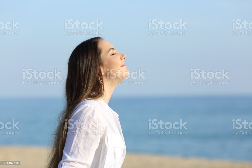 Woman relaxing breathing fresh air on the beach stock photo