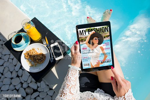 Unrecognizable female relaxing by the pool and reading emagazine on tablet at breakfast. All contents are made up.