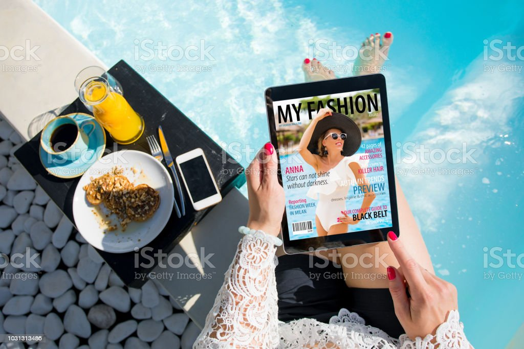 Woman relaxing by the pool and reading emagazine on tablet at breakfast. All contents are made up. stock photo