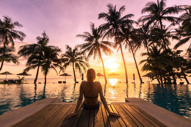 Woman relaxing by the pool in luxurious beachfront hotel resort stock photo