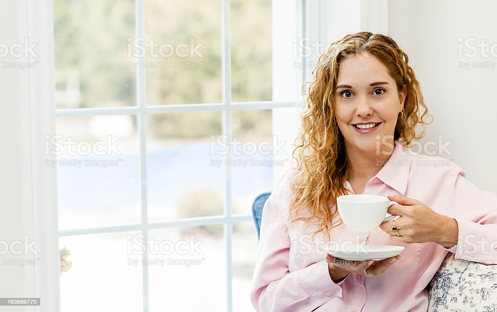 Woman relaxing by the window with beverage royalty-free stock photo