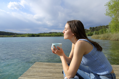 Profile of a woman relaxing drinking coffee in a lake pier