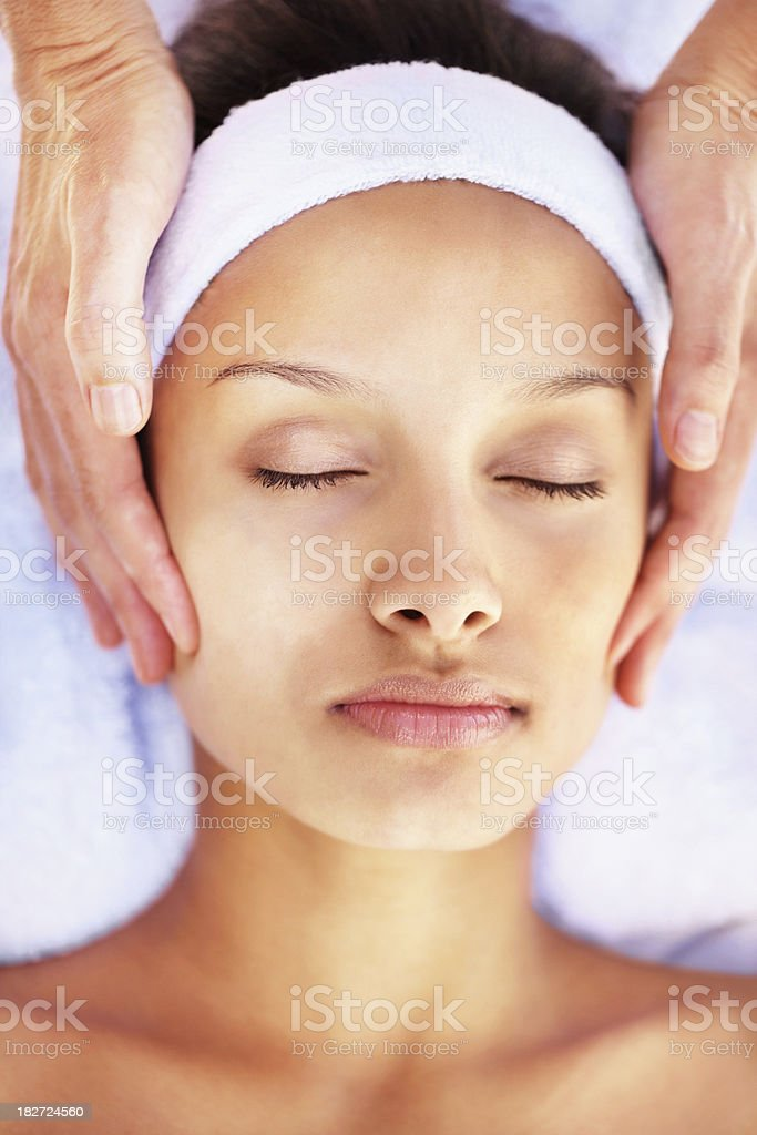 Woman relaxing during facial massage at a spa royalty-free stock photo