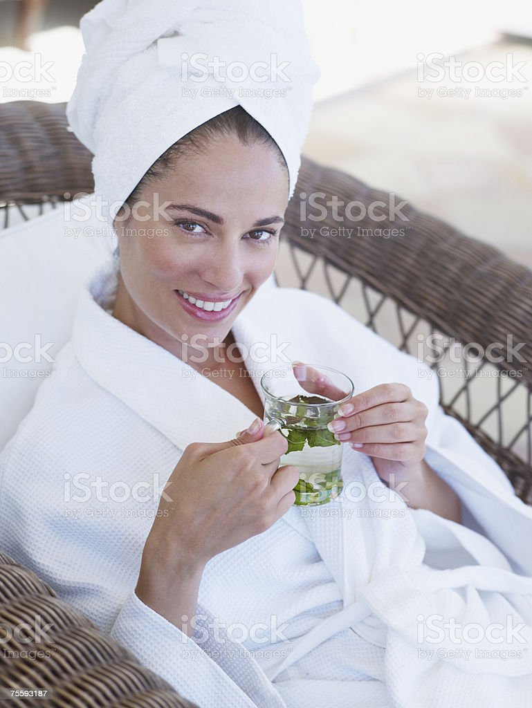 Woman relaxing in a bathrobe holding a health drink stock photo