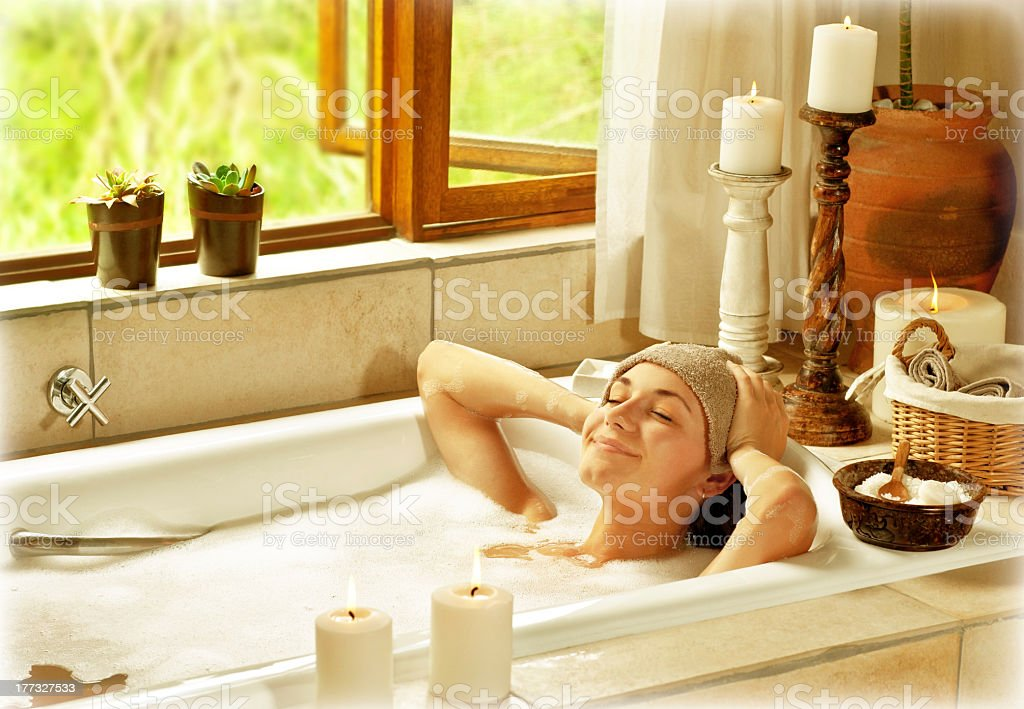 A woman relaxing in a bubble bath stock photo