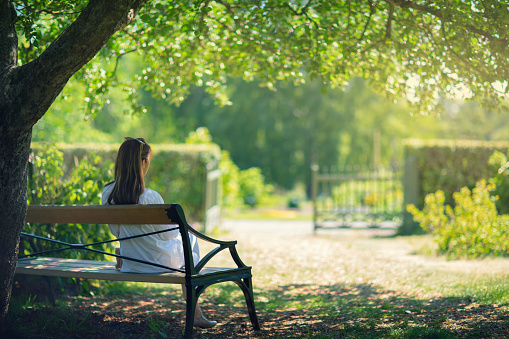 A woman sitting down on a bench in a garden in the shade of a tree and enjoying the surroundings.