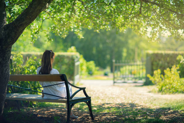 A woman relaxing in a green garden A woman sitting down on a bench in a garden in the shade of a tree and enjoying the surroundings. sitting stock pictures, royalty-free photos & images