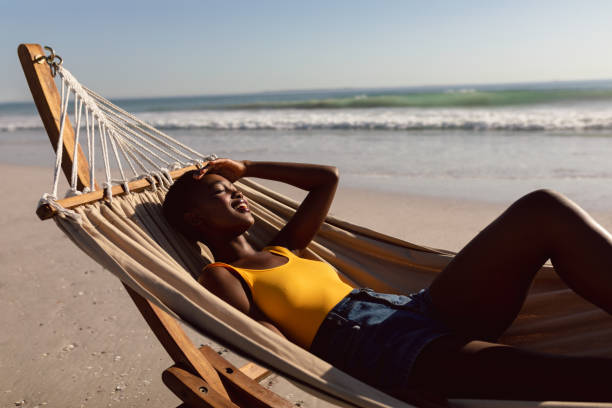 Woman relaxing in a hammock on the beach stock photo