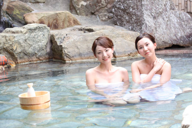 woman relaxing in a hot spring - hot spring stock photos and pictures