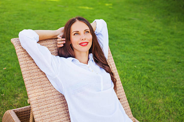 donna rilassante in una chaise longue - divano procrastinazione foto e immagini stock