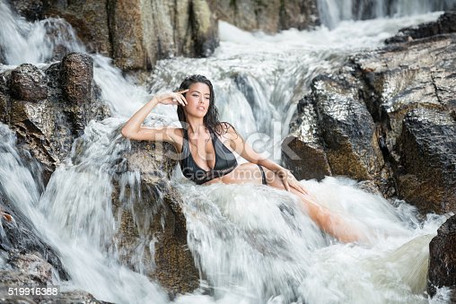 Beautiful woman relaxing in a natural waterfall spa of a mountain stream. Nikon D810. Converted from RAW.