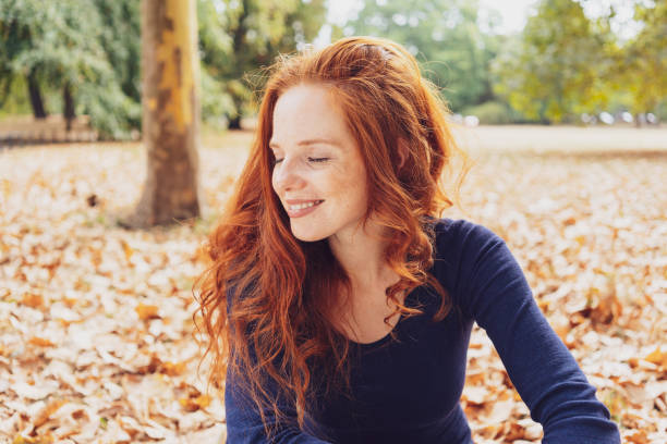 woman relaxing in a park smiling with pleasure - woman portrait forest foto e immagini stock