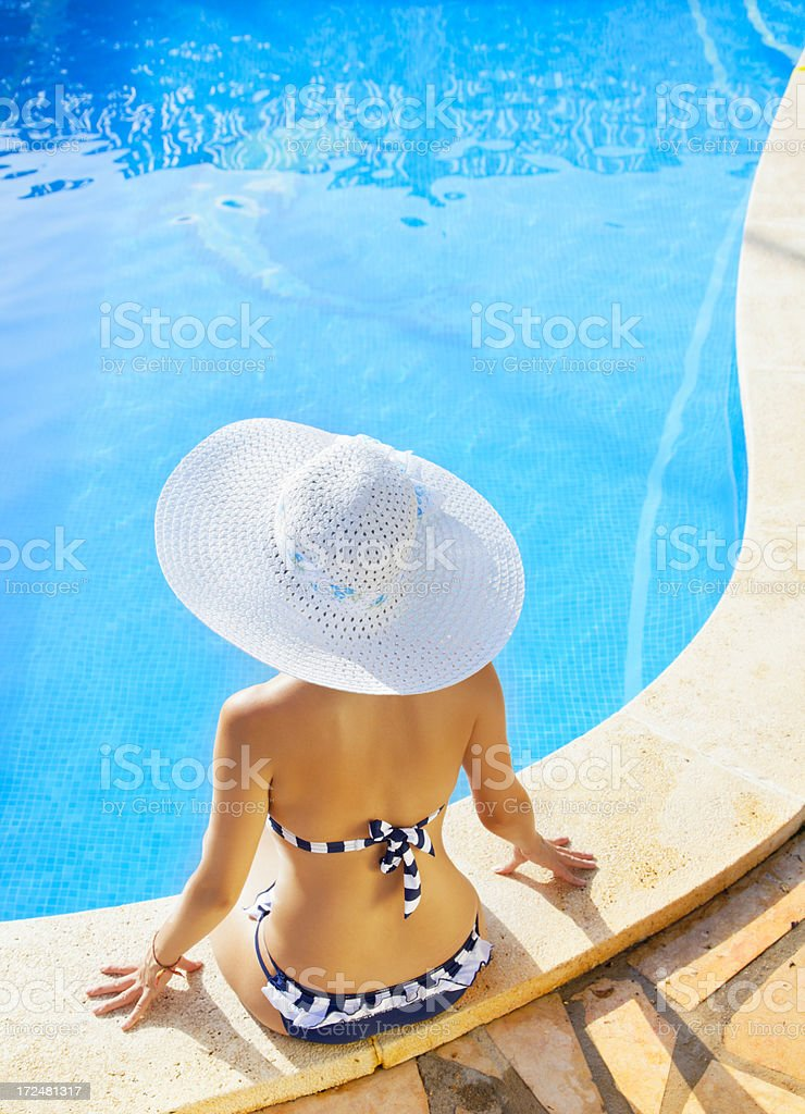 woman relaxing in a resort swimming pool stock photo