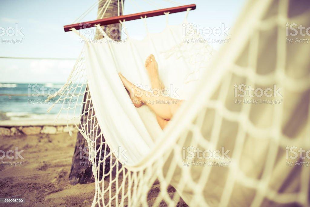 Mulher, relaxante numa rede branca na praia - foto de acervo