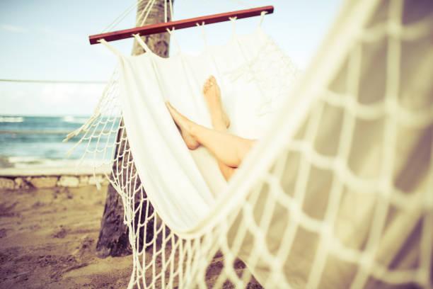 mujer relajante en una hamaca blanca en la playa - mujeres dominicanas fotografías e imágenes de stock