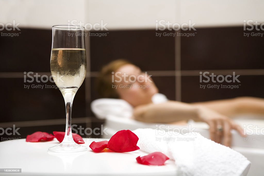 Woman relaxing in bath with glass of wine and rose petals royalty-free stock photo