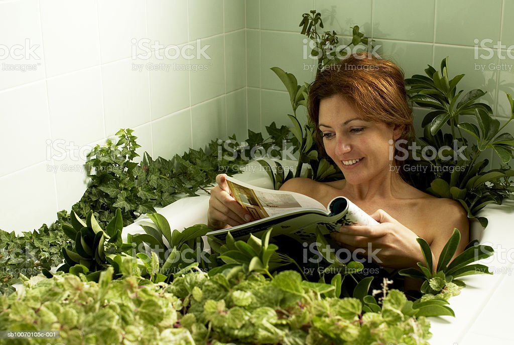 Woman relaxing in bathtub covered with plants, reading magazine royalty free stockfoto