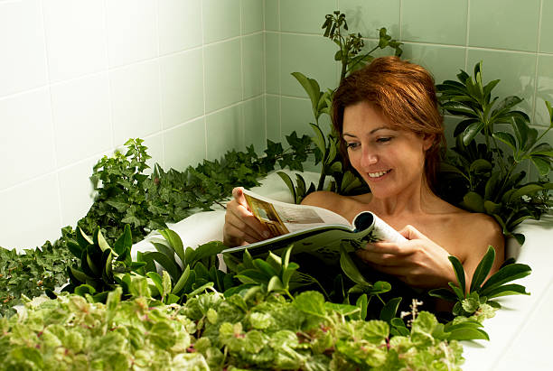 Woman relaxing in bathtub covered with plants, reading magazine stock photo
