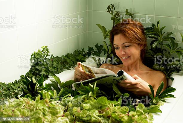 Woman Relaxing In Bathtub Covered With Plants Reading Magazine Stock Photo - Download Image Now