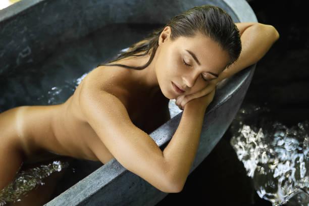 Woman relaxing in bathtub in open air bathroom stock photo