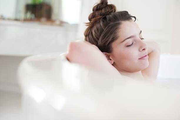 donna rilassante nel bagno pieno di schiuma - bacinella metallica foto e immagini stock