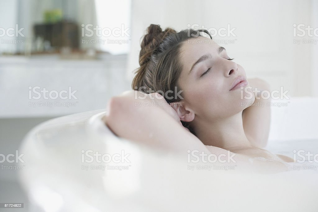 Woman relaxing in bubble bath stock photo