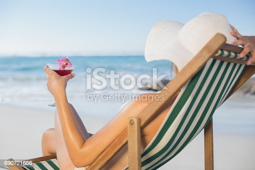 istock Woman relaxing in deck chair with cocktail 690721666