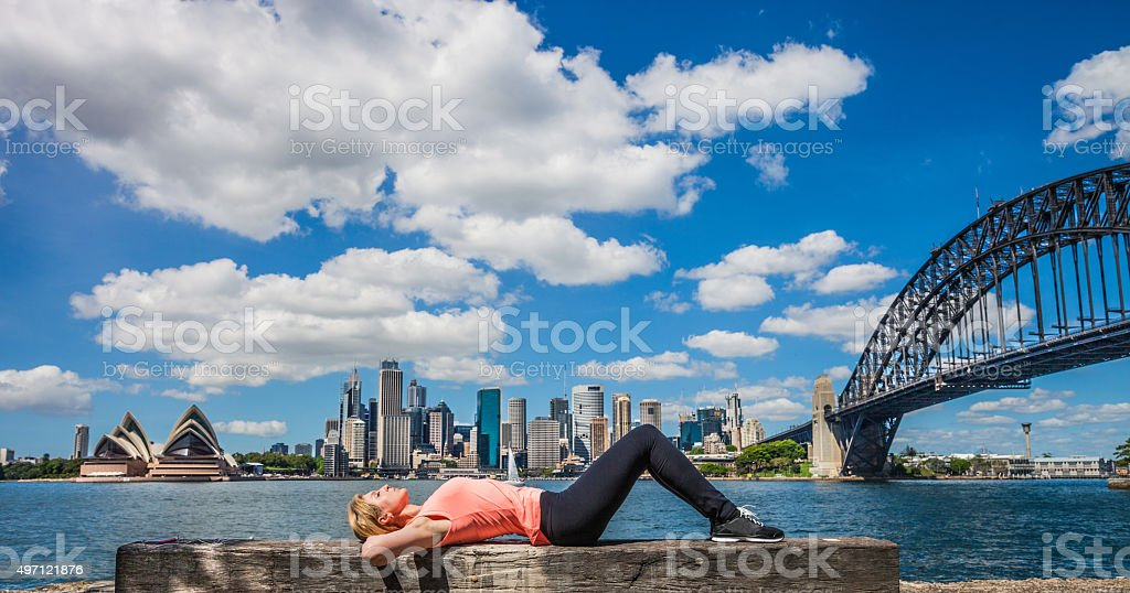 Woman relaxing in front of Sydney Harbor and city skyline stock photo
