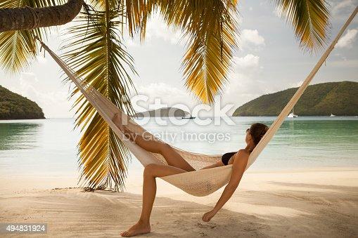 woman in black bikini relaxing in a hammock at a tropical beach at Maho Bay, St.John, US Virgin Islands