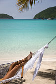 woman relaxing in hammock on a tropical beach in the Caribbean