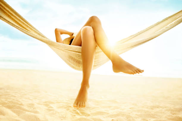 Woman relaxing in hammock on beach stock photo