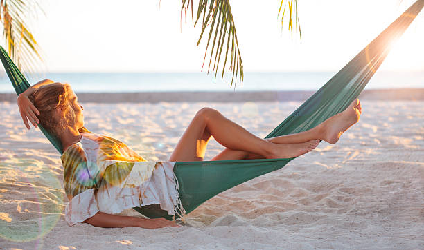 woman relaxing in hammock on beach - hangmat stockfoto's en -beelden