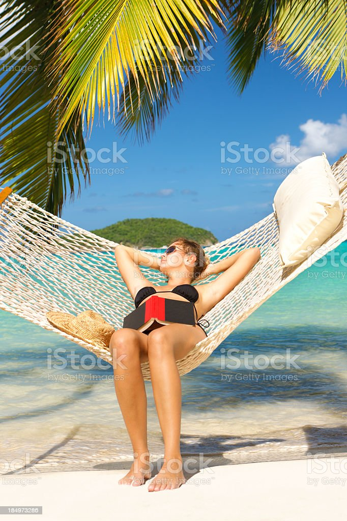 woman relaxing in hammock with a book at the beach stock photo